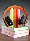Books and headphones as audio books concept on grey background poster
