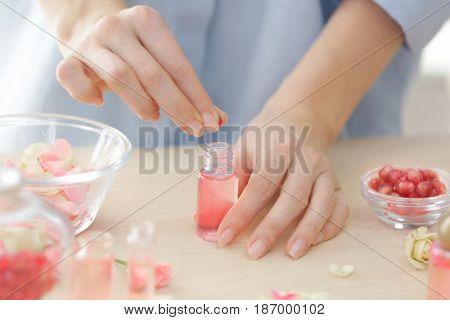 Woman making natural perfume with rose petals, closeup