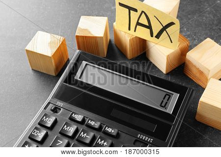 Paper note with word Tax, wooden cubes and calculator on table