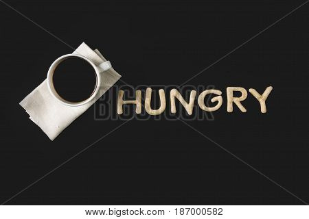 Top View Of Word Hungry Made From Cookie Dough And Coffee Cup Isolated On Black