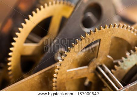 Industrial machinery bronze cog transmission macro view. Aged metal gear wheel teeth mechanism, shallow depth field selective focus.