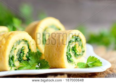 Cheese and parsley omelette rolls on a plate. Home fried omelette rolls with grated cheese and finely chopped parsley. Delicious vegetarian egg breakfast recipe. Rustic style. Closeup