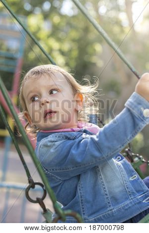 A two-year-old girl moves on a swing in the park while looking dangerously behind her back