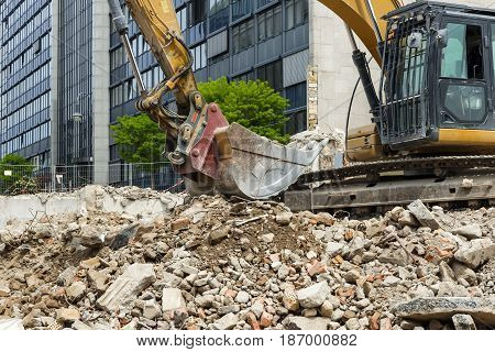 Bucket of a large excavator on a pile of construction debris