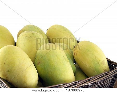 close-up mangoes in wicker basket isolated on white background, tropical fruit when ripe will have a sweet taste, when raw have a sour taste, used as an ingredient in many Asian foods
