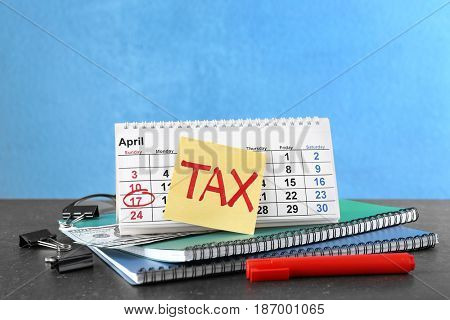 Paper sheet with word TAX, calendar and notebooks on table
