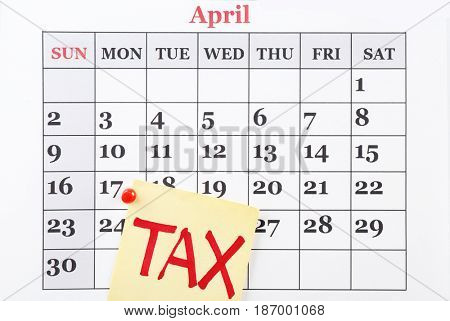 Paper sheet with word TAX pinned to calender