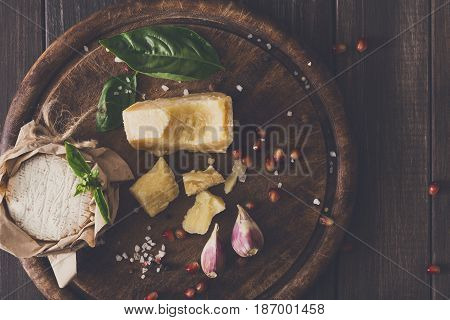 Parmesan, camembert and brie cuts on dark wood, top view