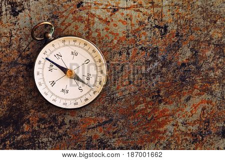 Retro magnetic compass on textured rusty metal background. Geographic exploration navigating instrument for searching direction journey. Up view, copy space.