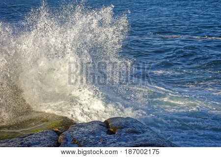 Wave crashing on the rocks of Arpoador stone at Ipanema beach Rio de Janeiro
