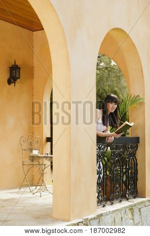 Pacific Islander woman reading book on patio