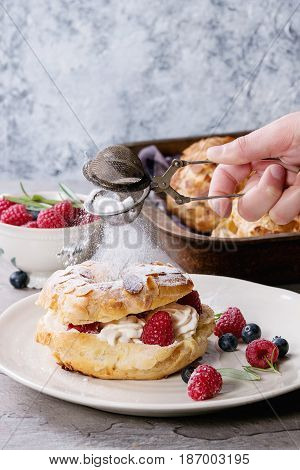 Filling and empty homemade choux pastry cake Paris Brest with raspberries, almond, sugar powder, rosemary on plate and oven tray with berries over gray texture background. Sprinkling powder sieve.