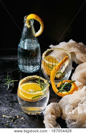 Tonic water cocktail with rosemary and orange. Two glasses and bottle with zest sugar and bubbles over black texture background with textile gauze. Refreshing beverage alco non alcohol
