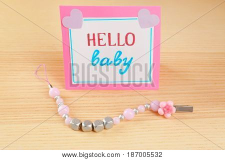 Pacifier clip for baby and greeting card on wooden table