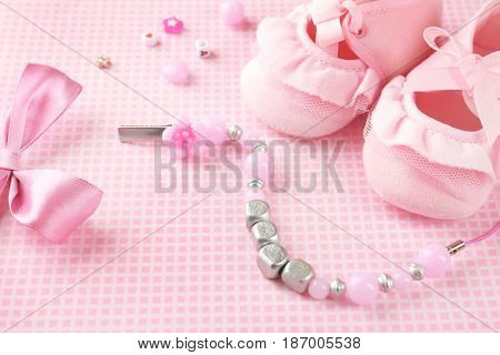 Composition with pacifier clip for baby, booties and bow knot on table
