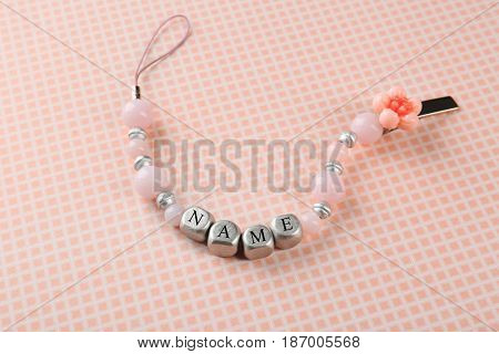 Beautiful pacifier clip with place for baby name on table