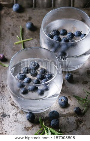 Tonic water cocktail with rosemary, blueberries. Two cold glasses over over dark texture metal background. Refreshing beverage alco non alcohol