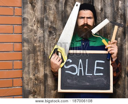 Bearded Painter Holding Various Building Tools And Board, Serious Face