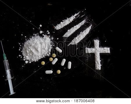 Cocaine drug powder pile, lines and cross, pills and injection syringe on black background