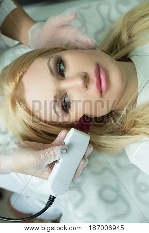Beautiful young girl on the procedure of skin rejuvenation in the beauty salon