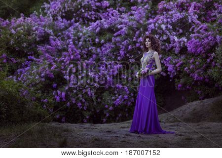 Woman against the background of blossoming lilac flowers she is dressed in a lilac dress.