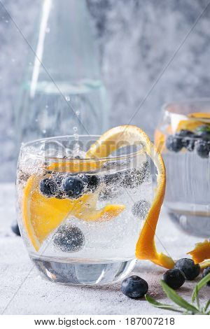 Tonic water cocktail with rosemary, blueberries and orange. Two cold glasses and bottle with zest and bubbles over gray blue texture background. Refreshing beverage alco non alcohol. Close up