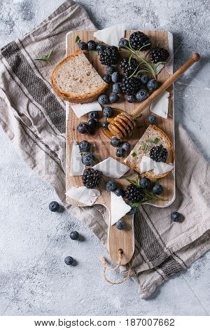 Berries blackberry and blueberry, honey on dipper, rosemary, sliced goat cheese with bread served on wooden board with textile linen over gray texture background. Summer sandwich. Top view with space
