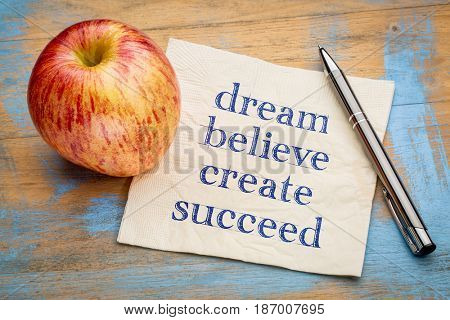 dream, believe, create, succeed - inspirational handwriting on a napkin with a fresh apple