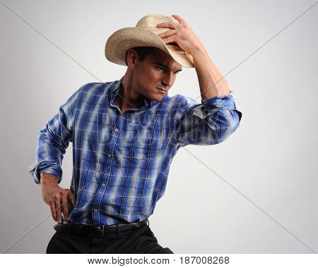 The sexy man is wearing a cowboy hat.