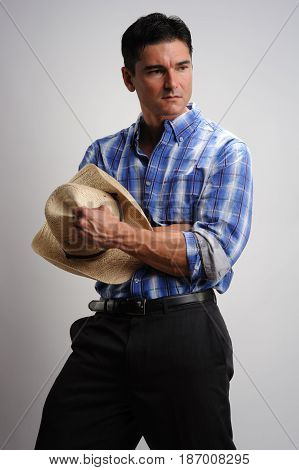 The handsome cowboy holds on to his hat.