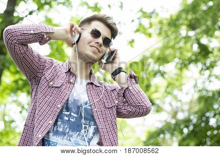Young Man Walks Through The Park, Listening To Music And Showing How Good Mood