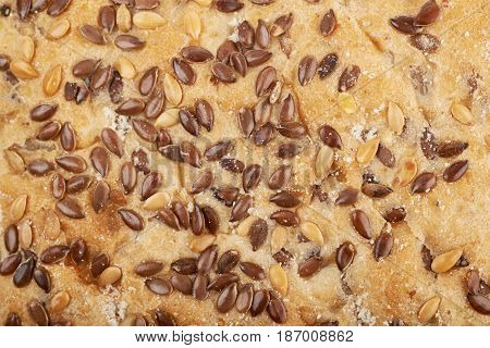 Close-up fragment of a sesame bread's crust as a backdrop texture composition