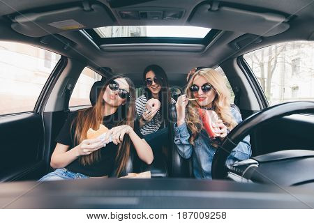 Three Girls Driving In A Car And Having Fun Eating Fast Food In Travel Road Trip