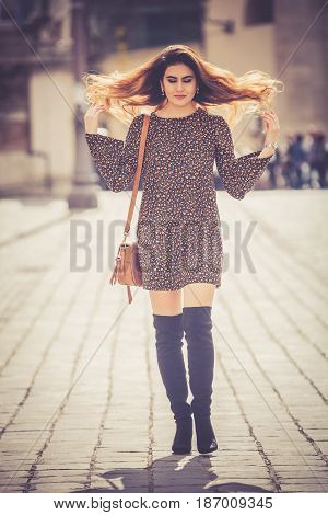 Beautiful and attractive young woman walking in the city. Red hair in the wind. Stylish dresses, urban style.