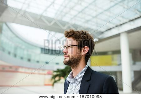 Portrait of young ambitious business executive in glasses