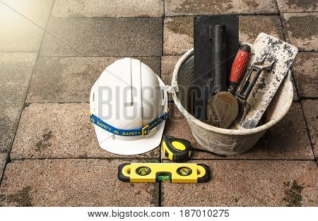 Construction tools or safety equipment with white helmet on brick ground