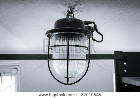 Old lantern in grid on the ceiling.