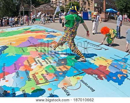 Volgograd Russia - June 12 2011: Clown walks on a puzzle of map of Russia on the Independence day of Russia in Volgograd