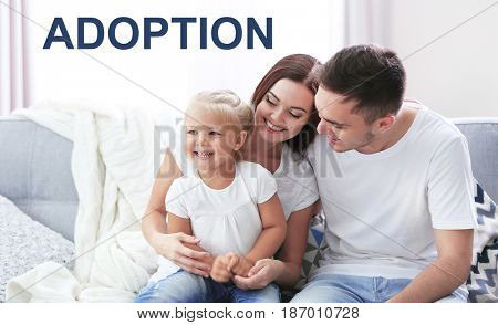 Adoption concept. Happy family sitting on couch at home