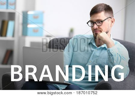 Brand marketing concept. Word BRANDING and man working with laptop on background
