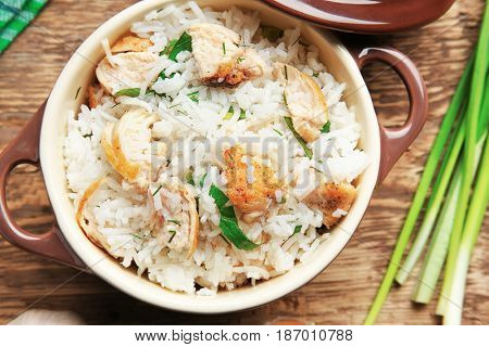 Tasty rice with chicken in saucepan on wooden table
