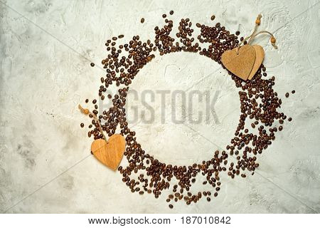 Circle silhouette made from coffee beans with wooden heart tags and copy space top view. Might be used as pie chart about coffee consumption.