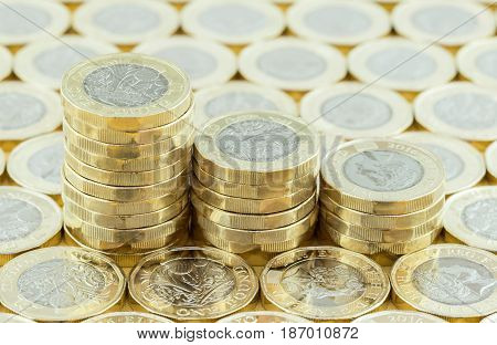 British money new pound coins in three stacks on a background of more money. New one pound coins introduced in 2017
