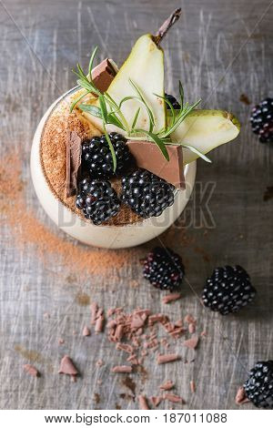 Dessert breakfast layered chia seeds, chocolate pudding, rice porridge in glass decorated by fresh blackberries, sliced pear, cocoa powder. Stand with spoon over gray texture background. Top view