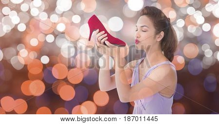 Digital composite of Young woman kissing new footwear over bokeh