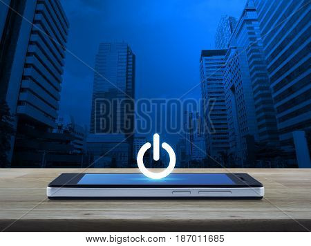 Power button icon on modern smart phone screen on wooden table over office city tower Start up business concept