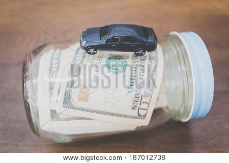 Car Model On Dollar Banknotes  On Wooden Background