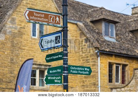 Bourton On The Water England - 7 April 2017 - Bourton On The Water street and information signs stand against yellow stone building on a cloudy spring day at Bourton On The Water England on April 7 2017.