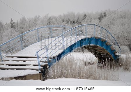 Bridge covered by snow in winter park.