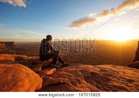 Hiker meets sunset at Grand view point in Canyonlands National park in Utah USA